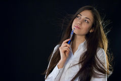 Beautiful woman holding blue pen. On black background Royalty Free Stock Photo