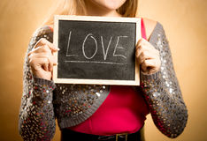 Beautiful woman holding board with word Stock Photos
