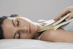 Beautiful Woman Holding Book While Sleeping In Bed Royalty Free Stock Photography