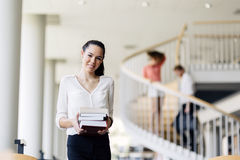 Beautiful woman holding books in a library Stock Photo