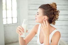 Beautiful woman holding a bottle of milk in her hand. Brunette girl wearing white singlet with Brown color Iroquois hair. Style Royalty Free Stock Photography