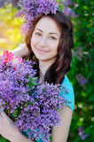 Beautiful woman holding a bouquet of lilacs in spring park Royalty Free Stock Image
