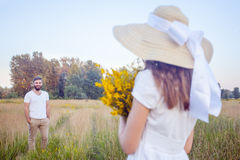 Beautiful woman holding bouquet of yellow flowers and looking at camera with her boyfriend on background. Royalty Free Stock Image