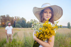 Beautiful woman holding bouquet of yellow flowers and looking at camera with her boyfriend on background. Stock Photo