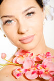 Beautiful woman holding a branch of orchid flowers Stock Photo