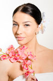Beautiful woman holding a branch of orchid flowers Royalty Free Stock Photos