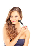 Beautiful woman holding a brush and applying make-up. Isolated on white background Royalty Free Stock Images
