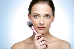 Beautiful woman holding brush for makeup Stock Photos