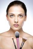 Beautiful woman holding brush for makeup. Closeup portrait of a beautiful woman holding brush for makeup Stock Photos