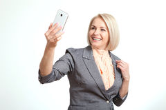 Beautiful woman holding camera and making selfie and smiling while standing against white background royalty free stock photography