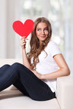 Beautiful woman holding a cardboard heart Stock Images