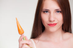 Beautiful woman holding carrot. And smiling Stock Photography