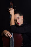 Beautiful woman holding a cello with selective light and black d Stock Photo