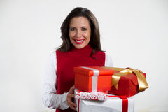 Beautiful woman holding Christmas gifts. Isolated brunette girl smiling and holding gift boxes royalty free stock photo