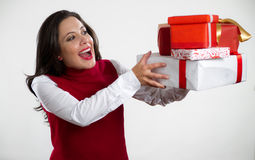 Beautiful woman holding Christmas gifts. Isolated brunette girl smiling and holding gift boxes royalty free stock photography