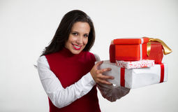 Beautiful woman holding Christmas gifts. Isolated brunette girl smiling and holding gift boxes stock photo