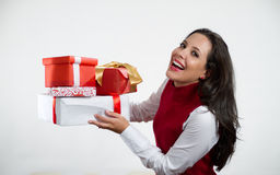 Beautiful woman holding Christmas gifts. Isolated brunette girl smiling and holding gift boxes royalty free stock photos