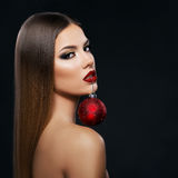 Beautiful woman holding a Christmas ornament with teeth over dark background royalty free stock photo