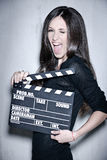 Beautiful woman holding clapperboard. Sensuality beautiful woman with long hair, dressed in black posing in studio, holding clapperboard Royalty Free Stock Images