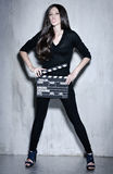 Beautiful woman holding clapperboard. Sensuality beautiful woman with long hair, dressed in black posing in studio, holding clapperboard Royalty Free Stock Photos