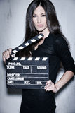 Beautiful woman holding clapperboard. Sensuality beautiful woman with long hair, dressed in black posing in studio, holding clapperboard Royalty Free Stock Image