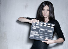 Beautiful woman holding clapperboard. Sensuality beautiful woman with long hair, dressed in black posing in studio, holding clapperboard Royalty Free Stock Photo