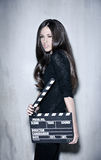 Beautiful woman holding clapperboard. Full portrait of sensuality woman with beautiful long dark hair, posing at studio, wearing black, holding clapperboard Stock Photos
