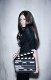 Beautiful woman holding clapperboard. Full portrait of sensuality woman with beautiful long dark hair, posing at studio, wearing black, holding clapperboard Royalty Free Stock Photography