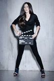 Beautiful woman holding clapperboard. Full portrait of sensuality woman with beautiful long dark hair, posing at studio, wearing black, holding clapperboard Royalty Free Stock Photo