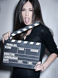Beautiful woman holding clapperboard. Portrait of sensuality woman with beautiful long dark hair, posing at studio, wearing black, holding clapperboard Royalty Free Stock Photos
