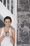 Beautiful Woman Holding Coffee Mug While Leaning On Door Frame Stock Photo