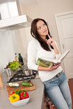 Beautiful woman holding cookbook in the kitchen Royalty Free Stock Photos