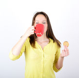 Beautiful woman holding cookies and coffee against white backgro Stock Photos
