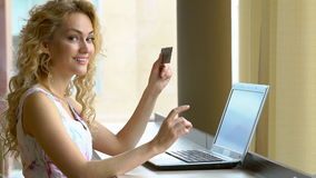 Beautiful woman holding credit card in hand and entering security code using laptop keyboard stock footage