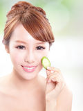 Beautiful woman holding cucumber slices on face Stock Images
