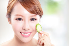Beautiful woman holding cucumber slices on face Stock Photo