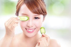 Beautiful woman holding cucumber slices on face Stock Photos