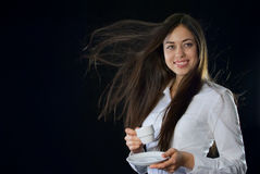Beautiful woman holding cup of coffee. On black background Stock Photos