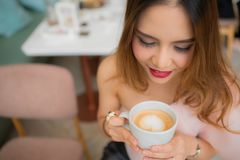 Beautiful woman is holding a cup of coffee in her hand on blur background coffee shop stock photos
