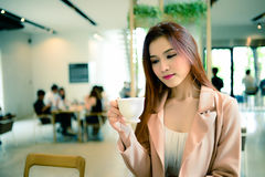 Beautiful woman holding a cup of coffee in her hand in blur background coffee shop, vintage style Royalty Free Stock Photo
