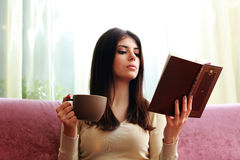 Beautiful woman holding cup of coffee and reading book Stock Photos