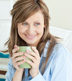 Beautiful woman holding a cup looking to the side Stock Image