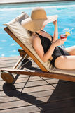 Beautiful woman holding drink by swimming pool Stock Images
