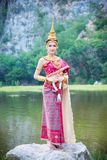 Beautiful woman holding flower and smiles. Beautiful asian woman in Thai traditional dress holding flower and smiles stock images