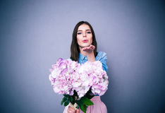 Beautiful woman holding flowers and sending kiss Stock Image