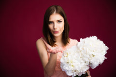 Beautiful woman holding flowers and sending kiss Stock Photo