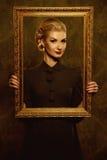 Beautiful woman holding frame Stock Photo