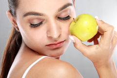 Beautiful woman holding a fresh apple with eyes closed Stock Images