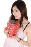 Beautiful woman holding gift box. And thinking over white background royalty free stock images