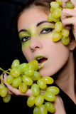 Beautiful woman holding green grapes closeup Stock Image